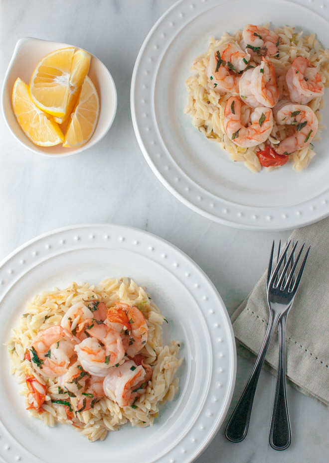Overhead of two plates of shrimp and orzo with lemon wedges on the side.