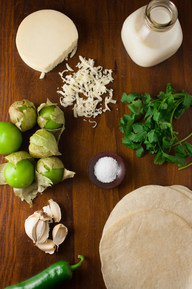Ingredients for making chicken enchiladas and tomatillo sauce spread out on a wooden table top
