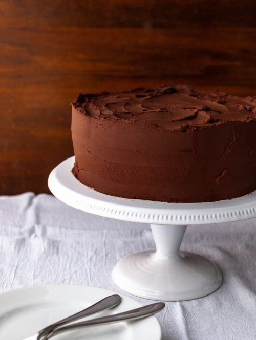 A chocolate cake with chocolate frosting on a white cake stand.