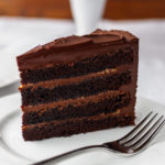 A slice of chocolate cake with caramel filling on a white plate.
