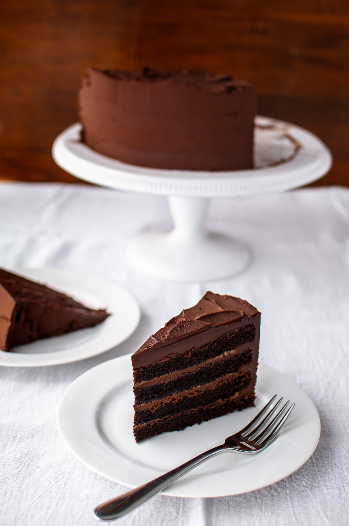 A slice of chocolate cake with caramel filling on a white plate next to a cake on a cake stand.