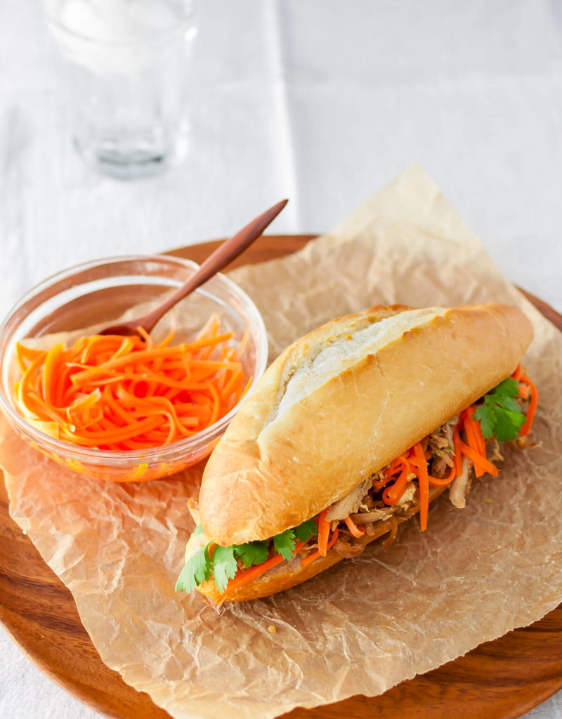 Roasted chicken banh mi sandwich with pickled carrots and cilantro on a wooden plate.