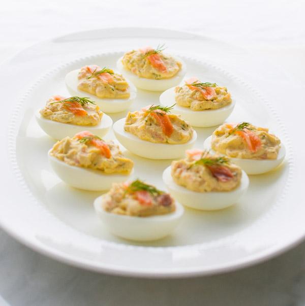 Deviled eggs on a white oval platter.