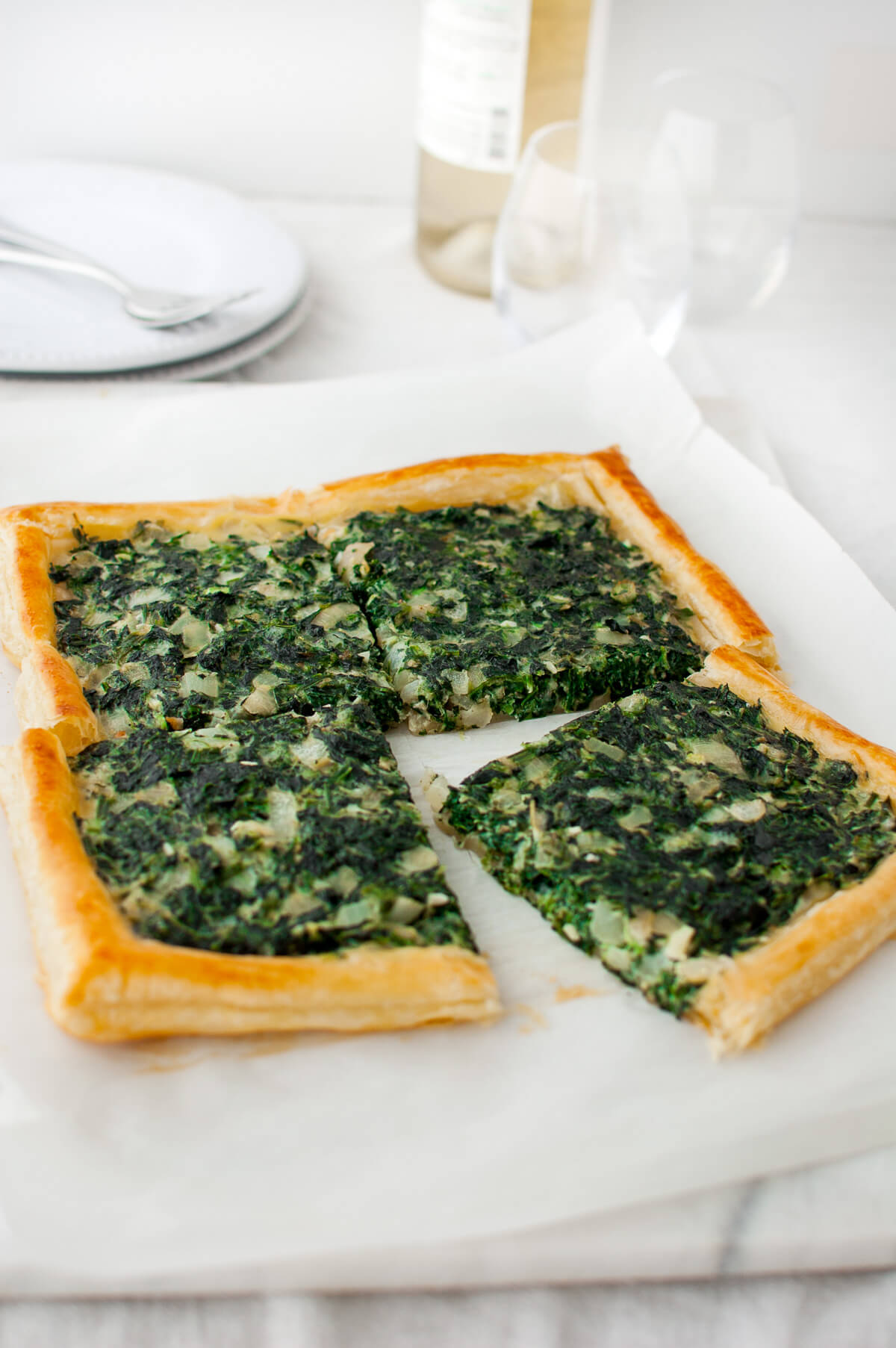 A spinach tart cut into four pieces on a marble board
