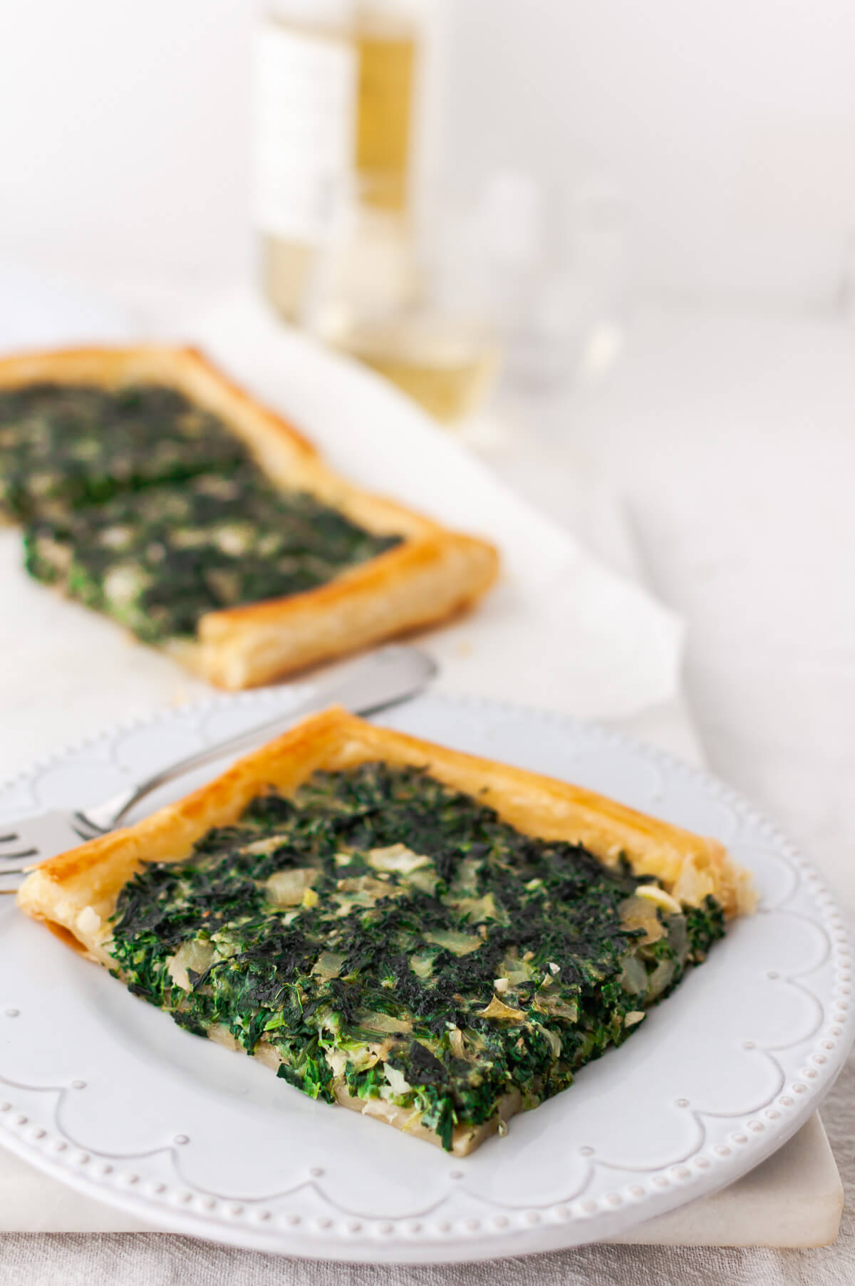 A piece of spinach tart on a white plate.