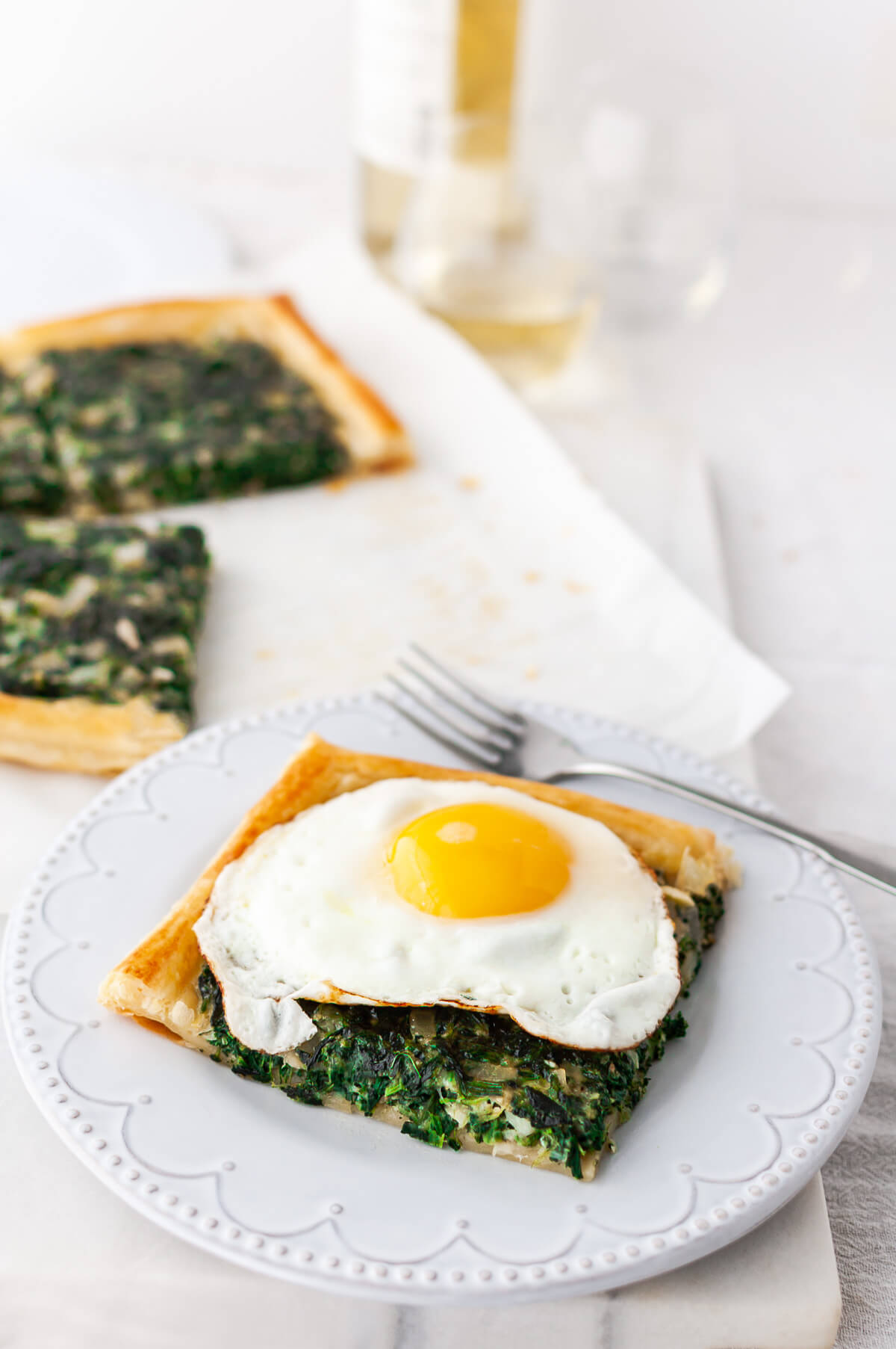 A slice of spinach tart with a fried egg on top.