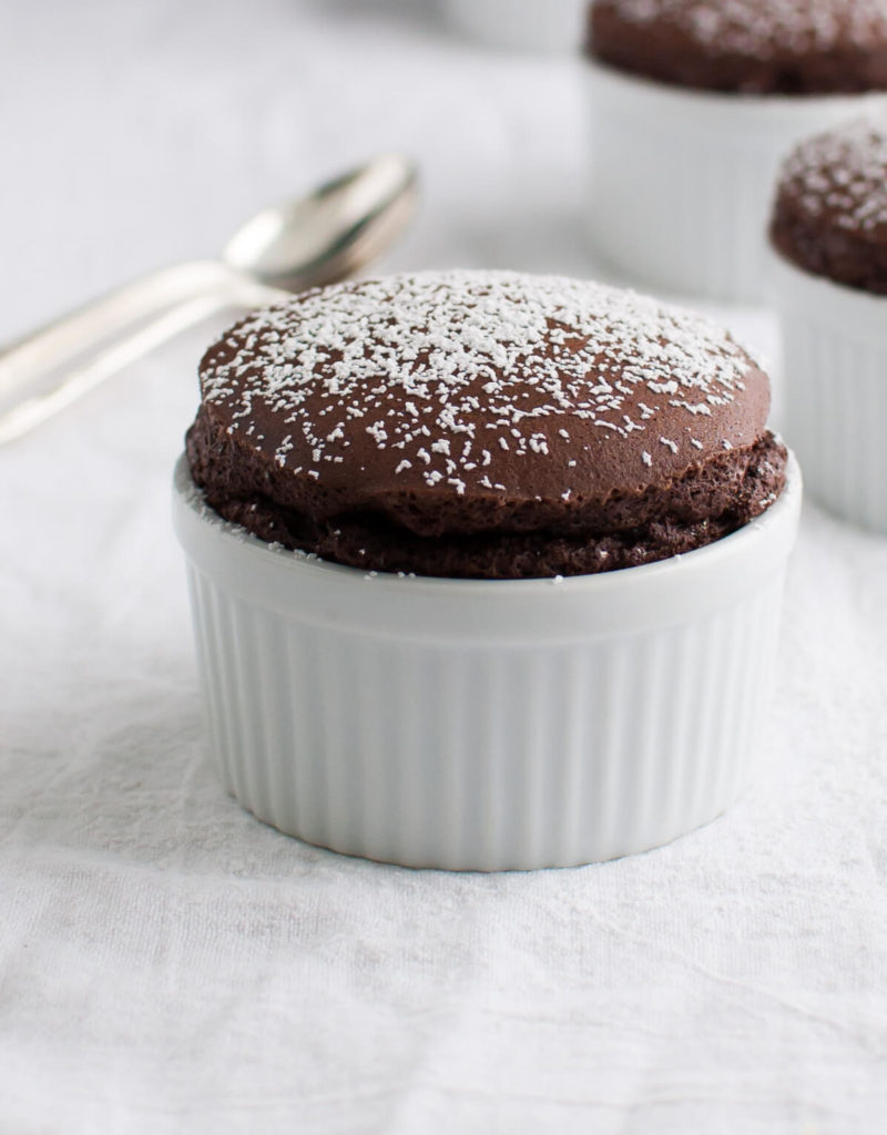 Several chocolate soufflés in small white ramekins sprinkled with powdered sugar.