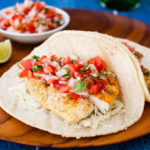Fish tacos with pico de gallo on a wooden plate.