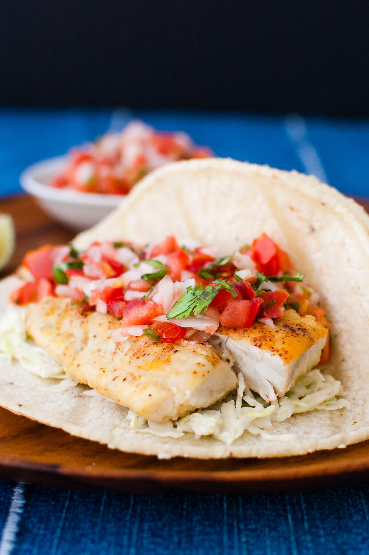 Close-up of a fish taco with pico de gallo on a wooden plate.