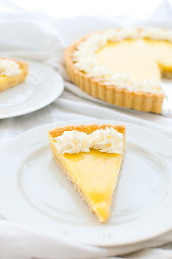 A slice of lemon tart on a white plate.