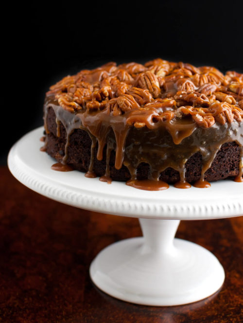 A chocolate cake topped with caramel sauce and toasted pecans on a white cake stand.