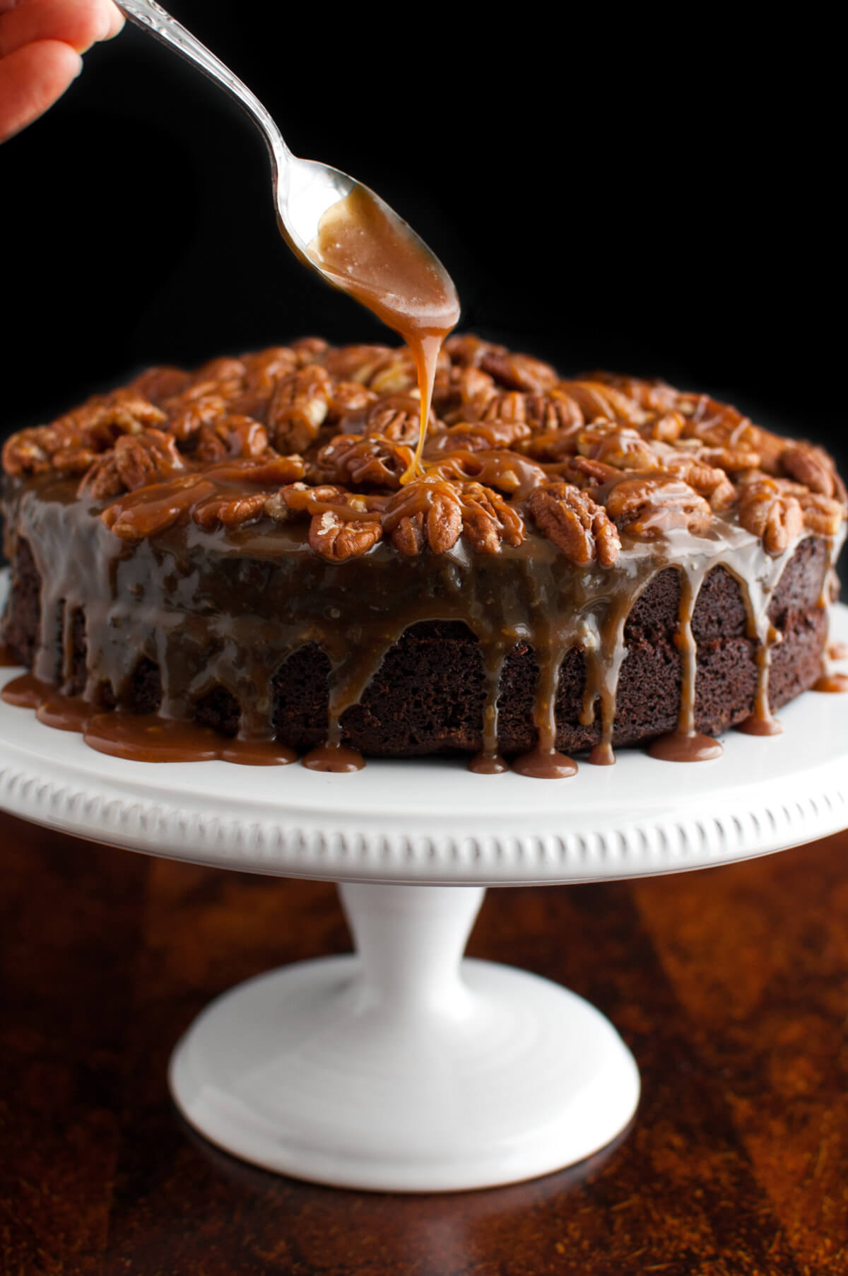Caramel sauce being dripped on a chocolate cake topped with pecans and more caramel sauce.