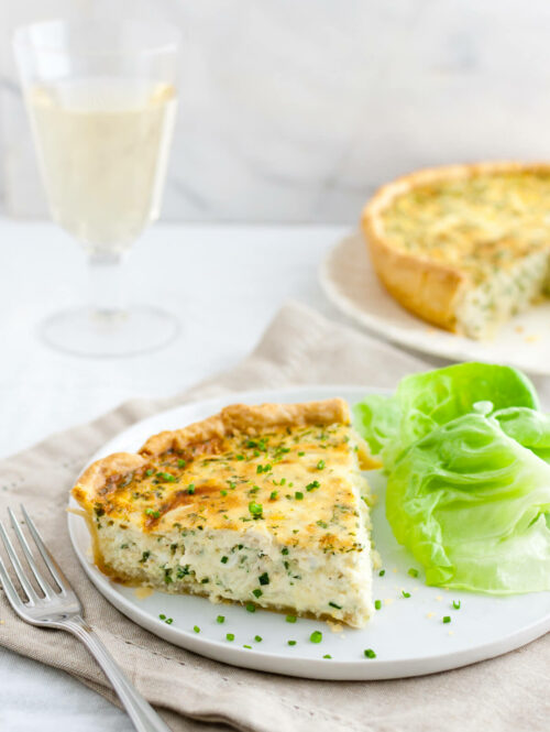 Crab quiche garnished with chopped chives served with a glass of white wine.