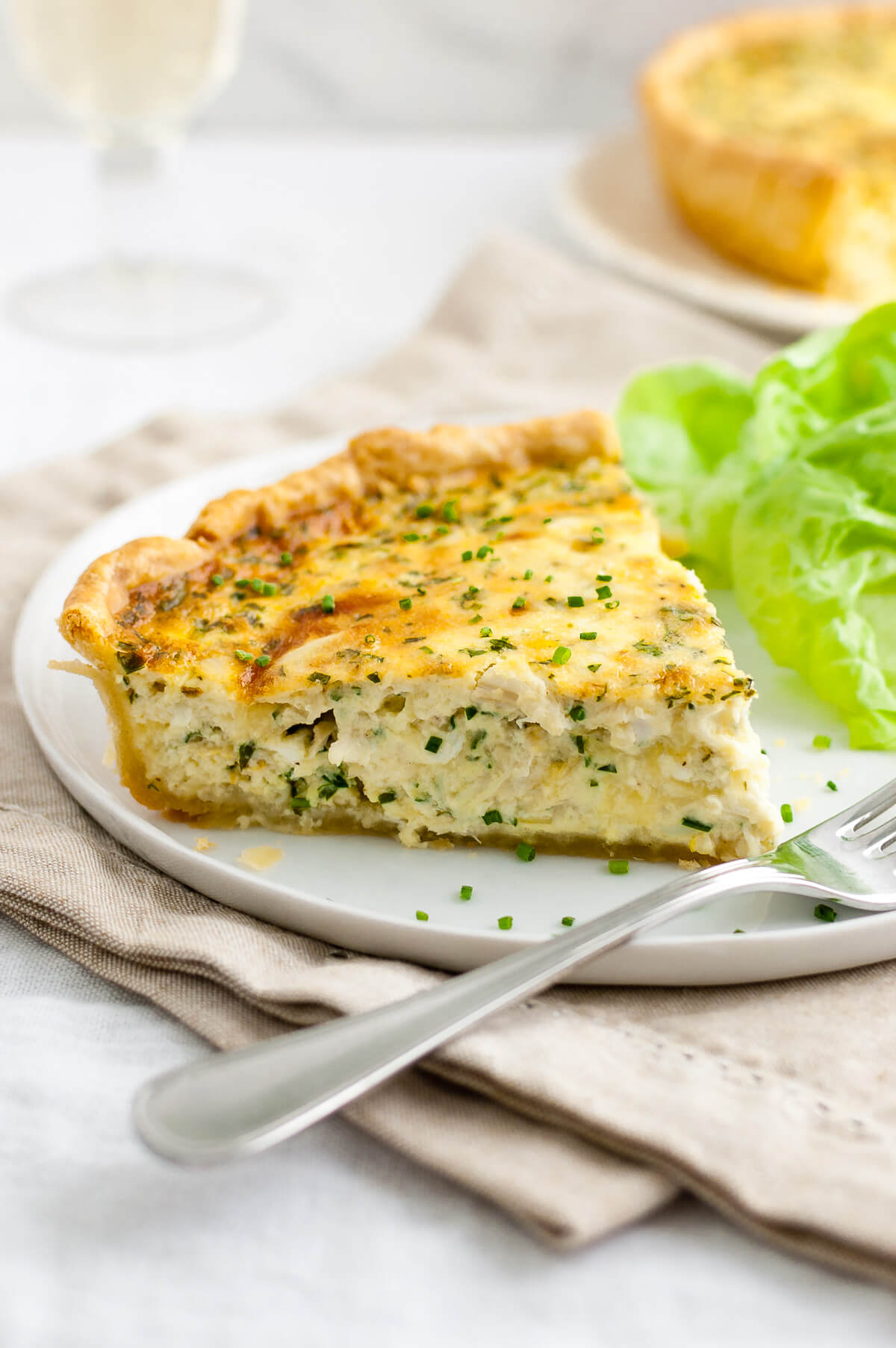 Close-up of a slice of crab quiche on a white plate.