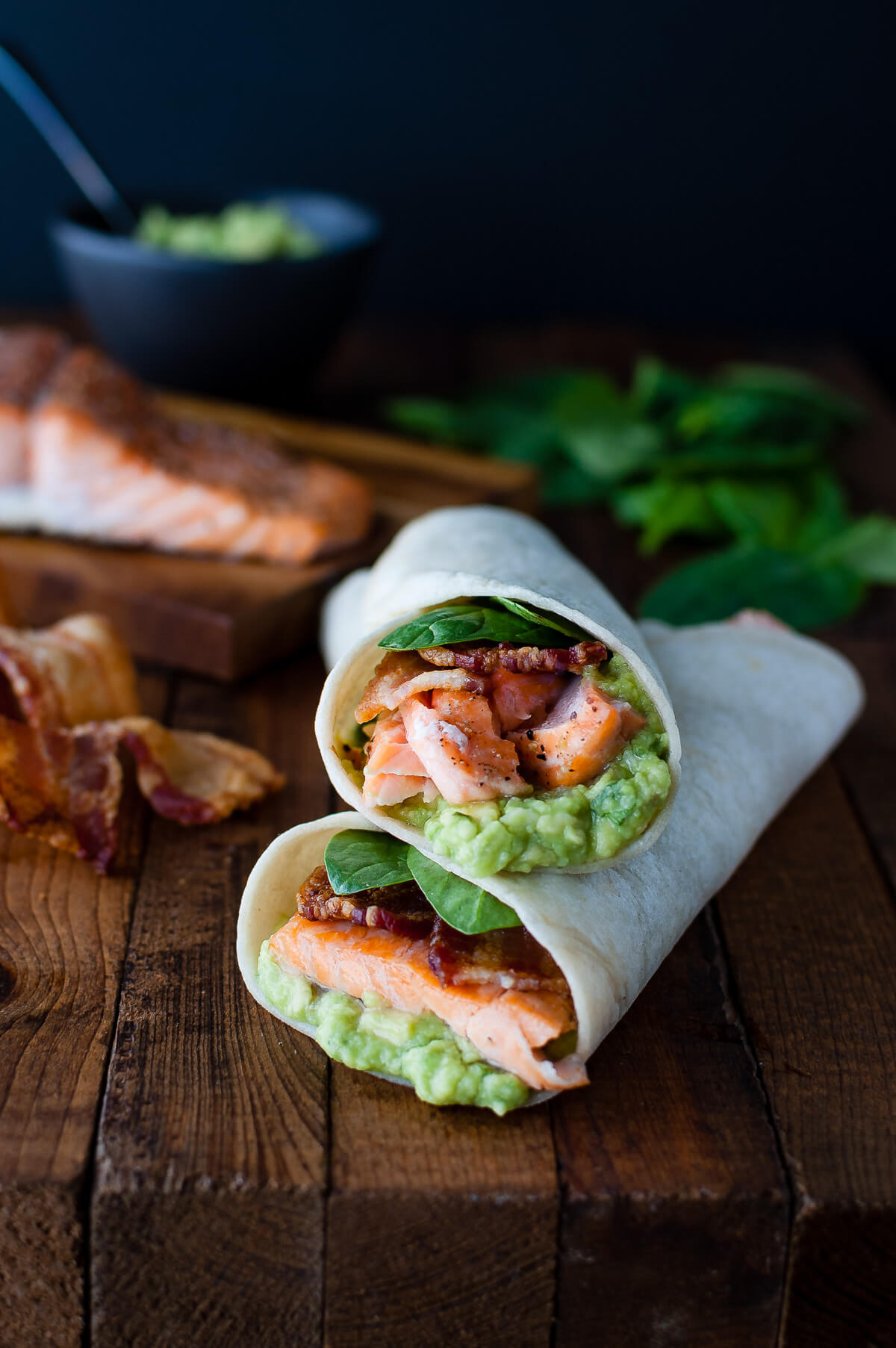 Salmon, guacamole, bacon, and spinach wrapped inside a tortilla on a wooden board.