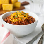 A bowl of chili topped with grated cheddar cheese.