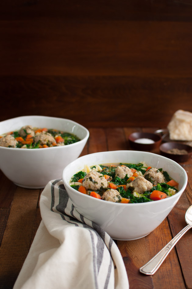 a hearty and flavorful soup full of spinach carrots orzo and meatballs