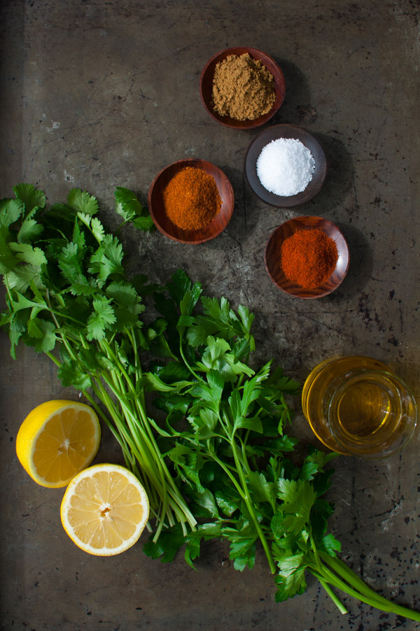 Ingredients for making chermoula sauce - spices, lemons, olive oil, parsley, and cilantro.