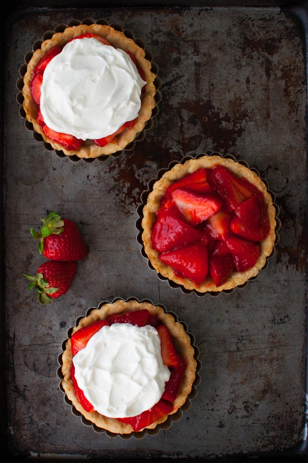 Individual Fresh Strawberry Pies - individual sized mini-pies with strawberries lightly sweetened with a fresh strawberry glaze topped with whipped cream in a flakey, buttery pie crust. | tamingofthespoon.com