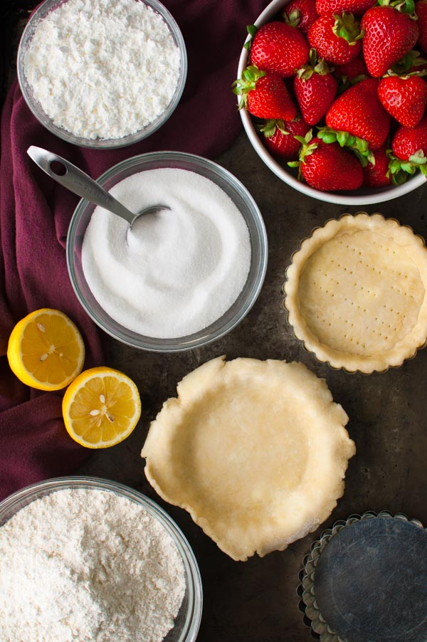 Ingredients for making fresh strawberry pies set out on a metal tray.