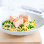 Plate of parmesan orzo with salmon and peas in a white bowl.
