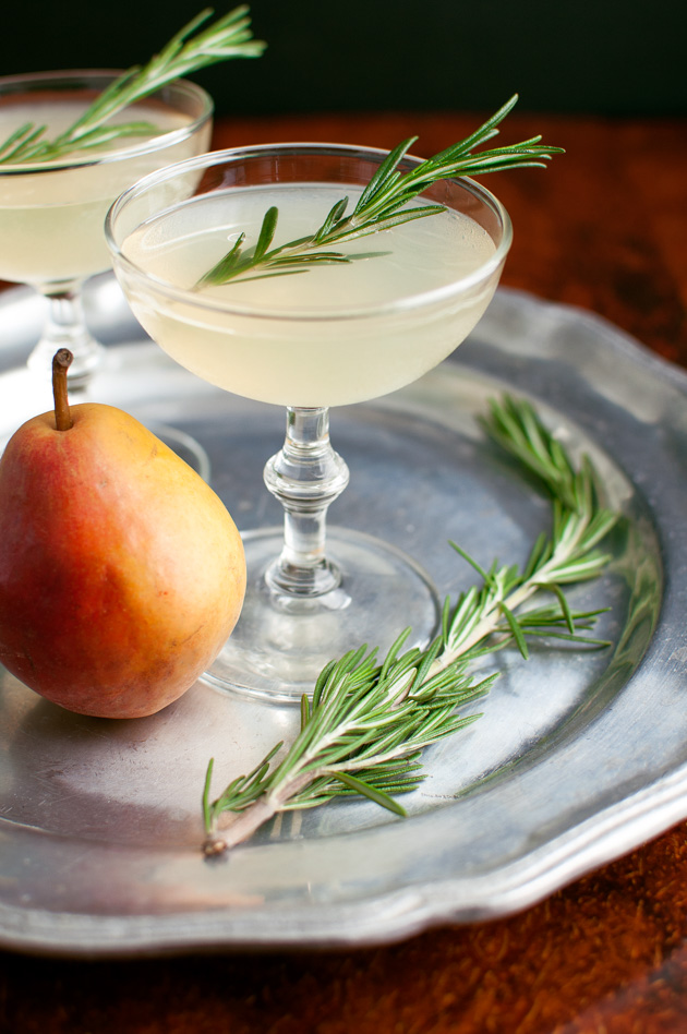 A pear-rosemary cocktail in a coupe glass garnished with a sprig of rosemary.