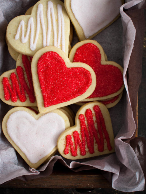 Decorated heart shaped sugar cookies in a tissue lined box.