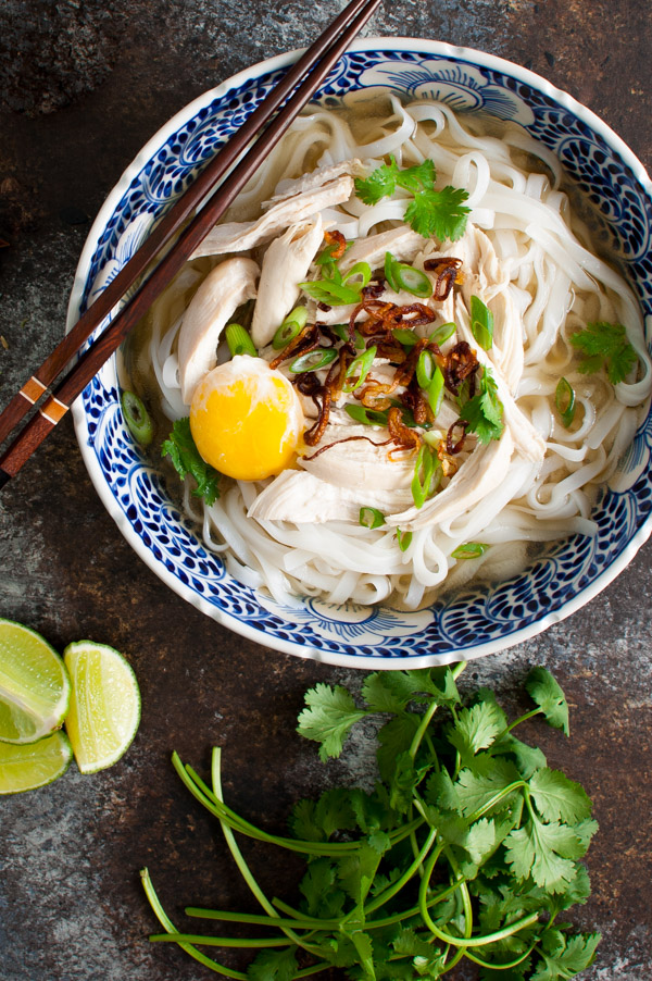 Bowl of chicken pho served with lime wedges, cilantro and an egg yolk.