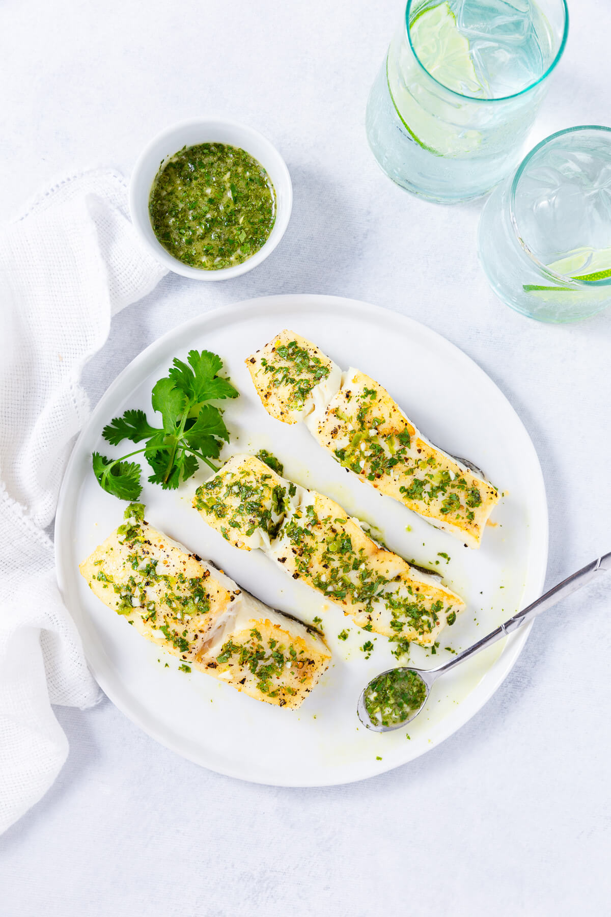 Overhead shot of three pieces of roasted halibut topped with cilantro-lime sauce.