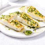 Roasted halibut topped with cilantro-lime sauce on a white plate.