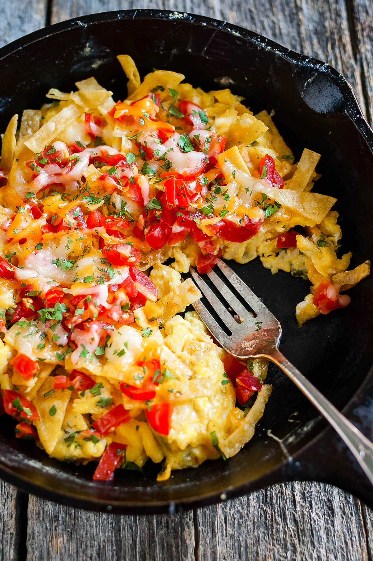Overhead view of migas topped with chopped tomatoes and melted cheese in a cast iron skillet.