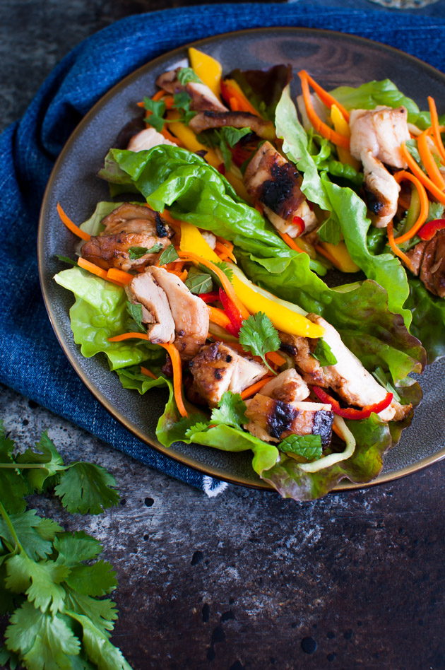 Grilled Chicken Lettuce Wraps - grilled asian marinated chicken thighs served with a cool slaw of carrots, cucumbers, and mango in lettuce leaves. | tamingofthespoon.com