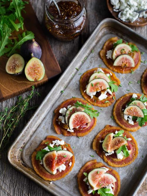 Overhead view of tray of pancetta crisps topped with goat cheese, figs, and baby arugula.