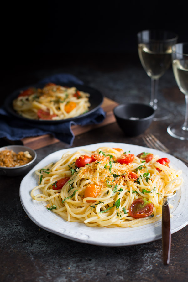 A plate of spaghetti topeed with tomatoes, basil, and toasted breadcrumbs.