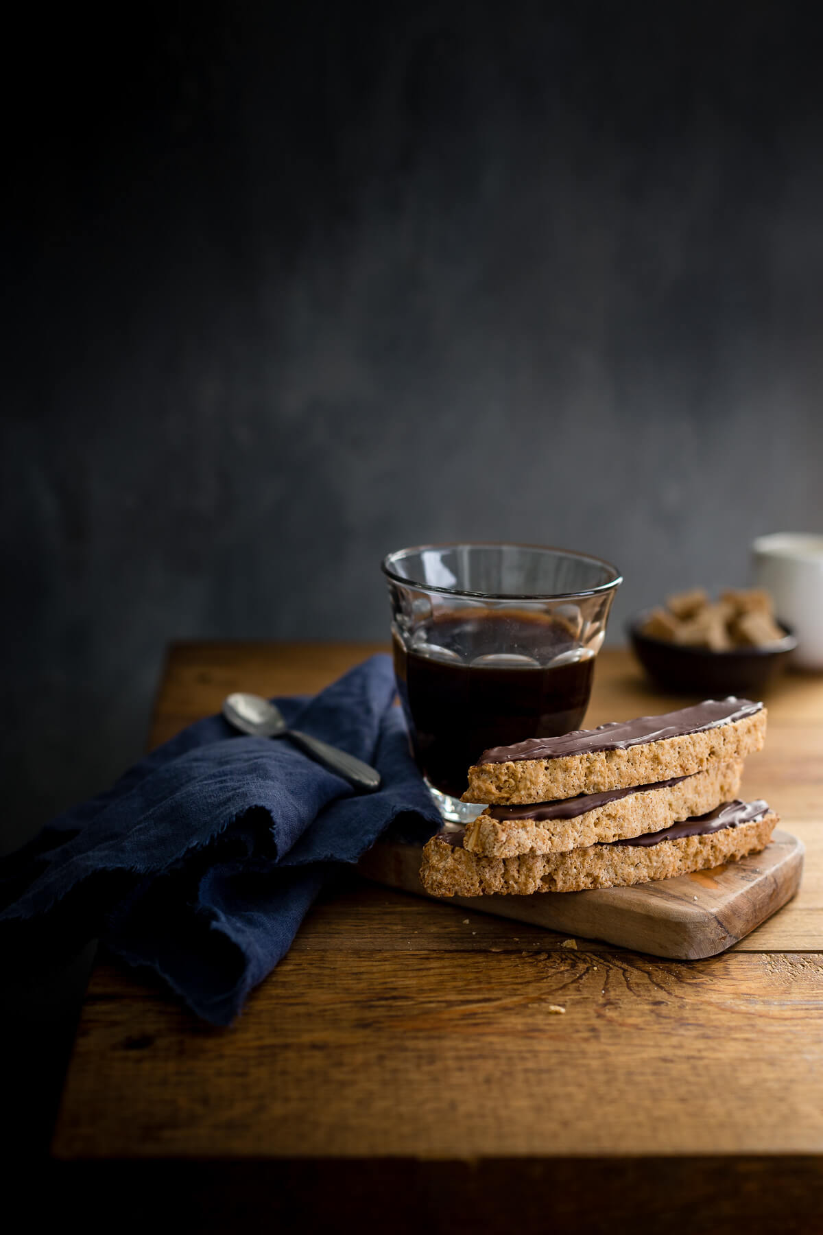 Almond biscotti and a cup of coffee on a small wooden board with a blue napkin.