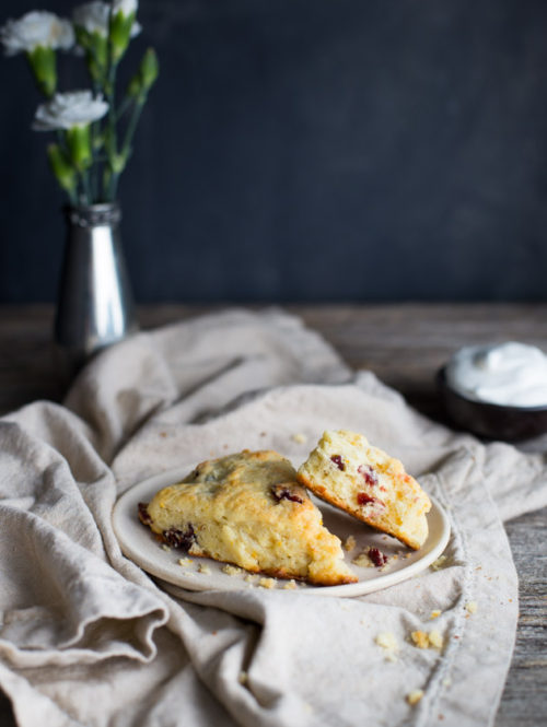 Two cranberry orange scones on a white plate with a linen napkin.