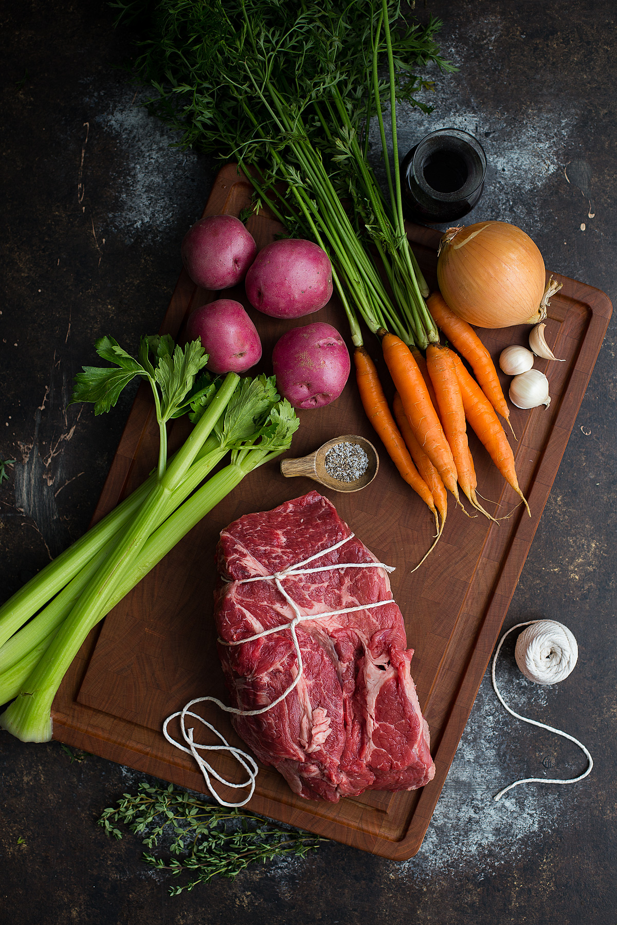 Ingredients for making a pot roast set out on a wooden cutting board.