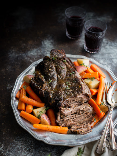 A pot roast on a serving platter with carrots and potatoes.