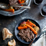 A serving of pot roast, carrots, and potatoes on a black plate.