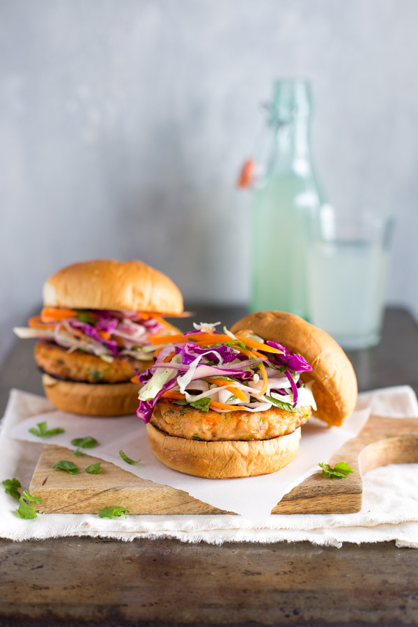 Two salmon burgers topped with cabbage slaw on a wooden serving board.
