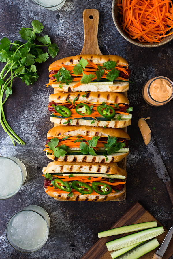 Overhead view of hot dogs topped with pickled carrots, cilantro, and sriracha mayo.