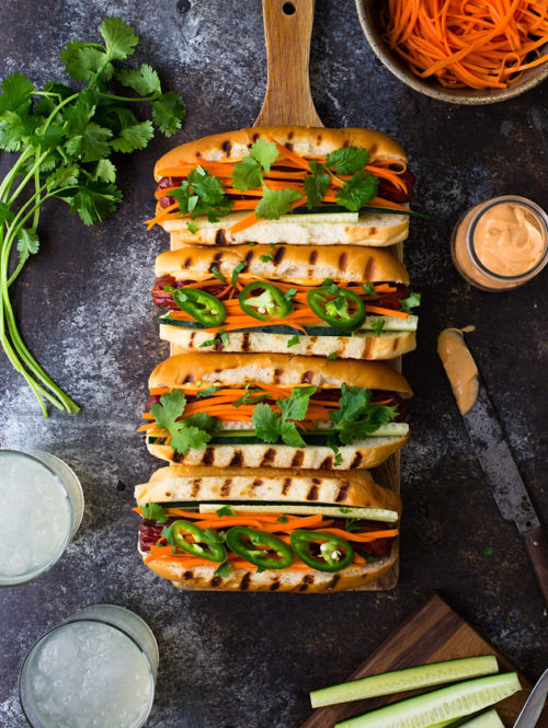 4 hot dogs topped with pickled carrots, cilantro, and sliced jalapeños on a wooden board next to glasses of lemonade.