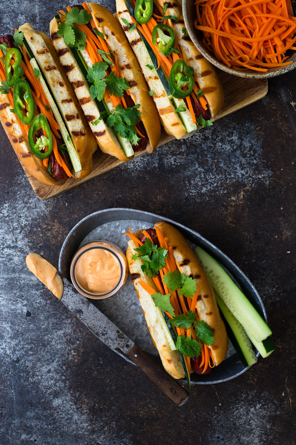 Overhead view of a hot dog on a metal tray topped with pickled carrots, cilantro, and sriracha mayo.