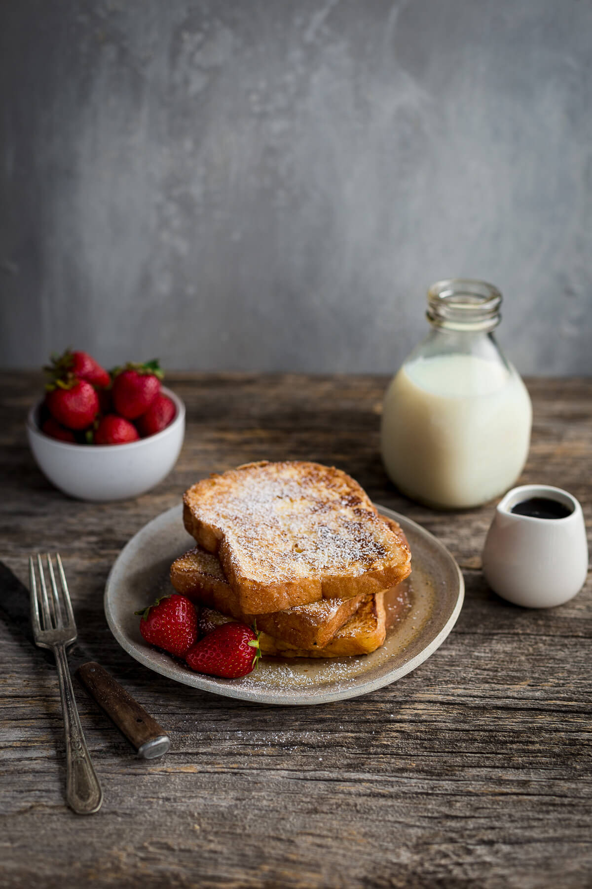 Slices of french toast dusted with powdered sugar served with strawberries.