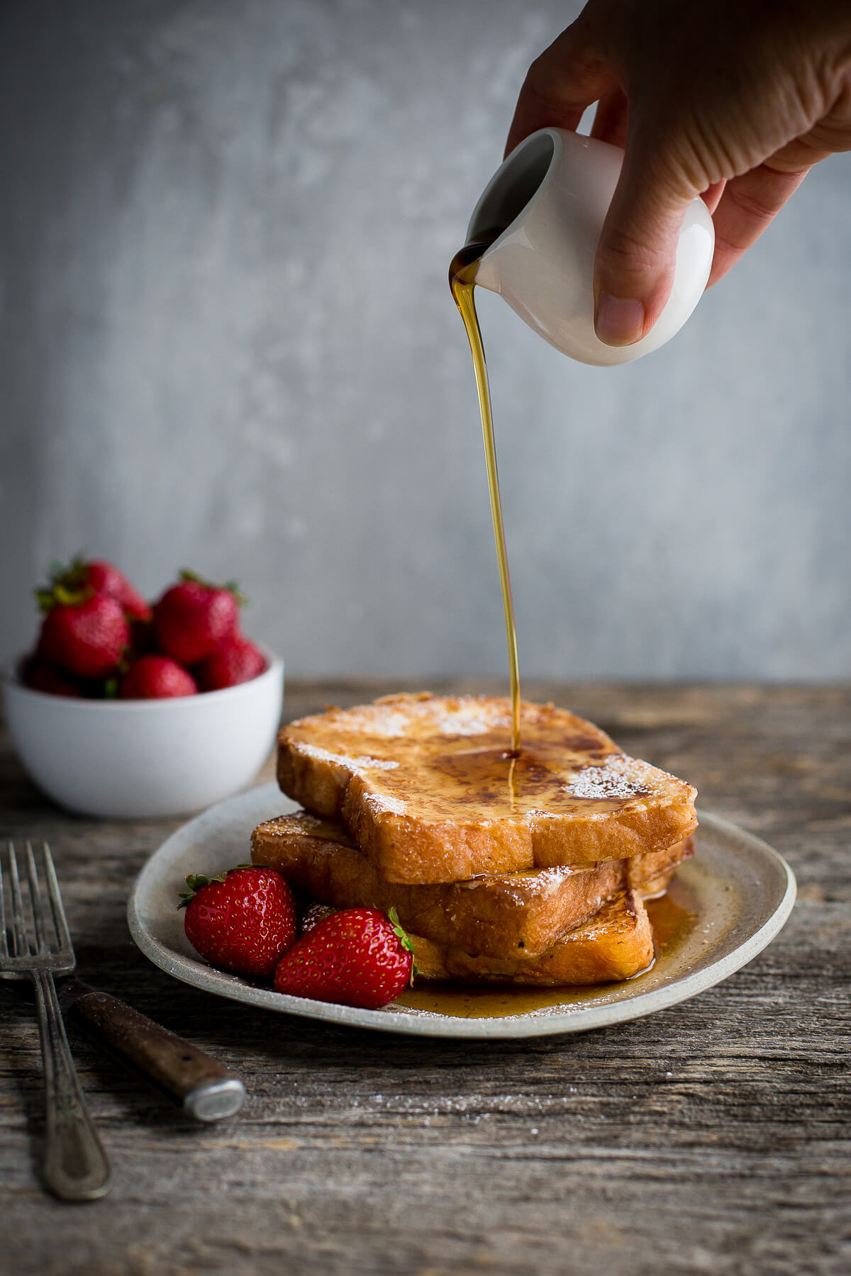 Syrup being poured on a stack of brioche french toast.
