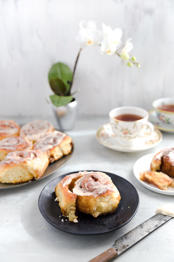 A breakfast scene with a large plate of cinnamon rolls, a cinnamon roll on a small plate, and some cups of tea.