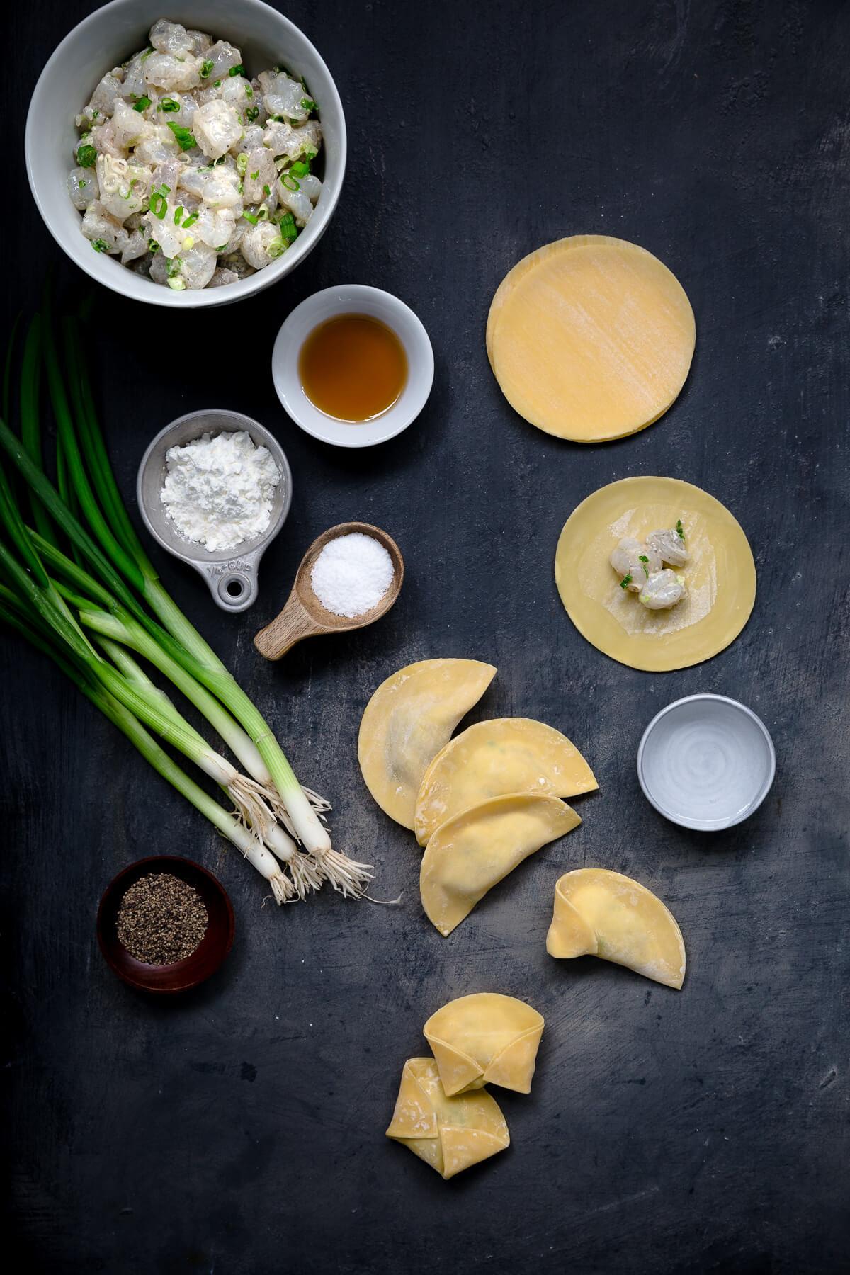 Ingredients for making shrimp dumplings set out on a dark gray board.