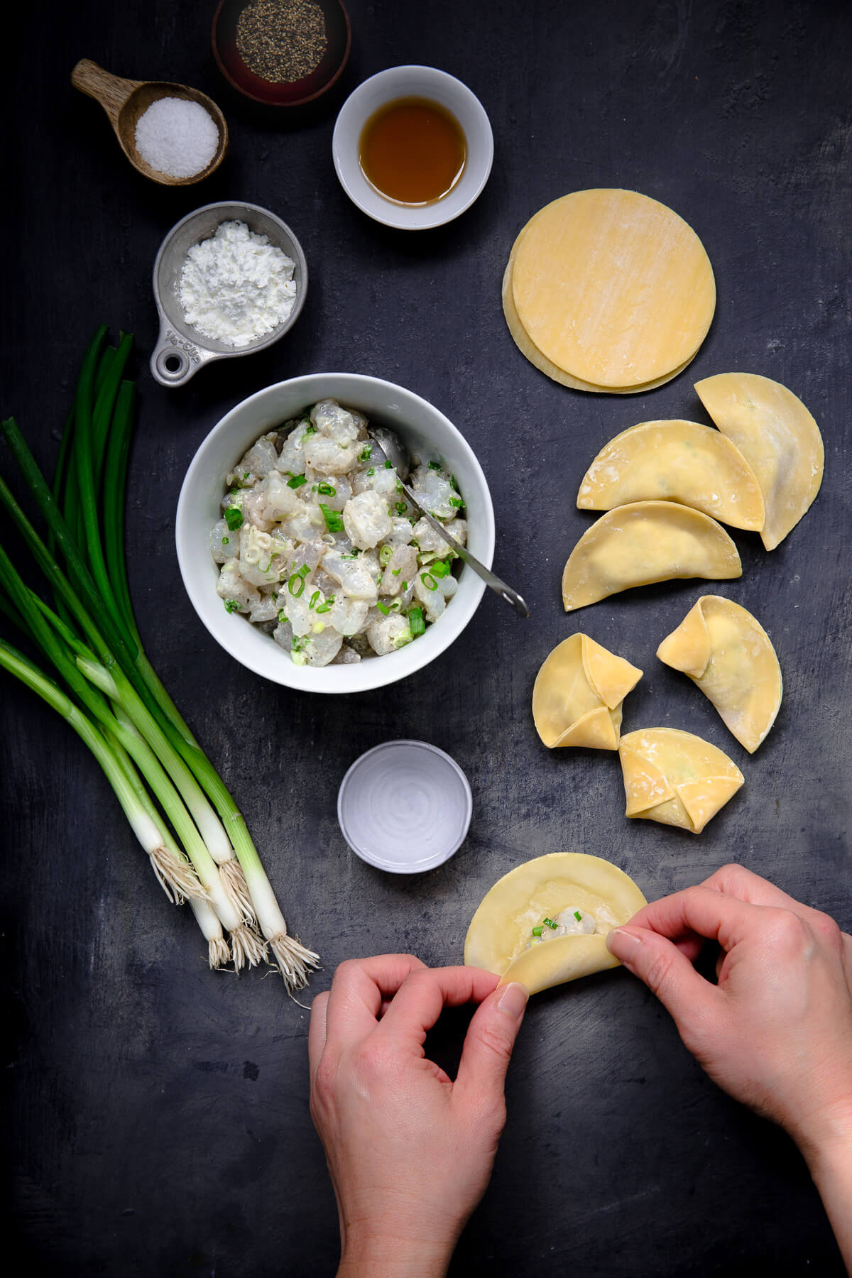 Overhead view showing someone making some shrimp dumplings for soup.
