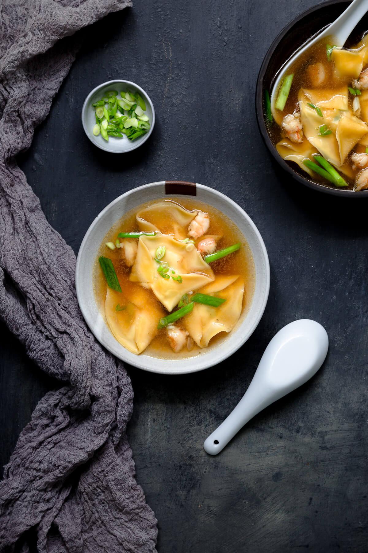 Overhead shot of two bowls of shrimp dumpling soup.