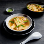A bowl of shrimp dumpling soup topped with chopped green onions.